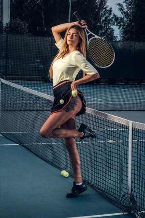 Attractive and young blonde girl is posing for photographer at tennis court while showing her leg tattoo. 版權商用圖片