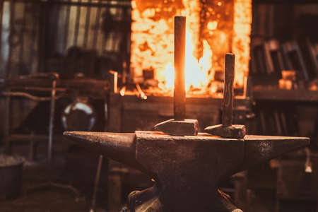 Dark stithy workshop with hammer on anvil at firs plan and fire in stove at background. 스톡 콘텐츠