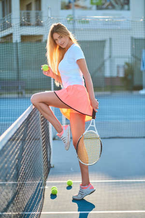 Beautiful young woman is playing tennis while posing for photographer. Stock fotó