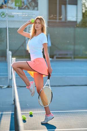Une jolie fille sportive pose pour le photographe sur un court de tennis avec une raquette par une belle journée d'été. Banque d'images