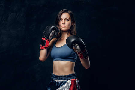 Portrait of serious female boxer in boxing gloves and sportive wear at dark photo studio.