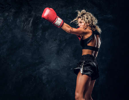 Sportive muscular woman is demonstrating her boxing exercises, wearing gloves.