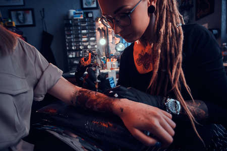 Young focused tattoo master is makining tattoo on clients hand at dark tattoo salon.