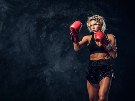 Blonde experienced boxer is demonstrating her tactic attack wearing special gloves. Stok Fotoğraf