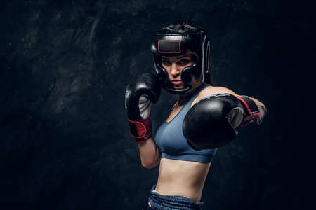 Portrait of attractive boxer in protective helmet and gloves ready to fight.
