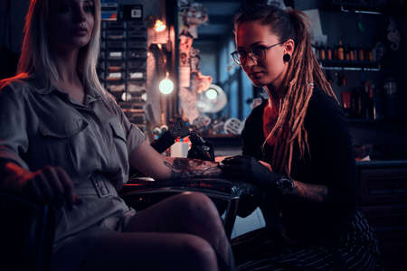 Expirienced tattoo artist is making tattoo for attractive young woman at tattoo salon.