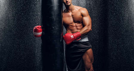 Young muscular man in red boxer gloves is posing with punching bag at dark room with water splashes on the wall.