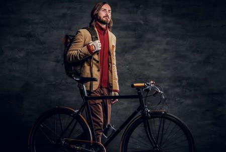 Hipster alla moda in giacca è in piedi nello studio fotografico scuro con la sua bici retrò.