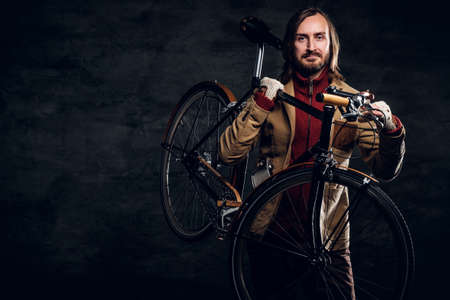 Modern bearded hipster in red sweater is holding his bike while posing for photographer.