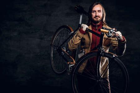Moderner bärtiger Hipster im roten Pullover hält sein Fahrrad, während er für den Fotografen posiert.