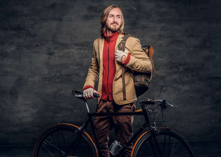 Modern bearded hipster in red sweater is holding his bike while posing for photographer. Archivio Fotografico