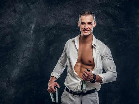 Szczęśliwy uśmiechnięty mężczyzna w białej koszuli pokazuje swój idealny sześciopak po otwarciu koszuli.