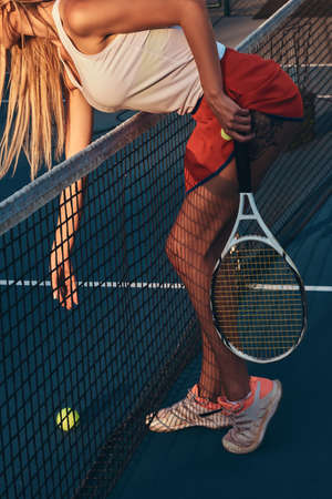 Sportive girl with tattoo is leaning to take a tennis ball over net at tennis court.