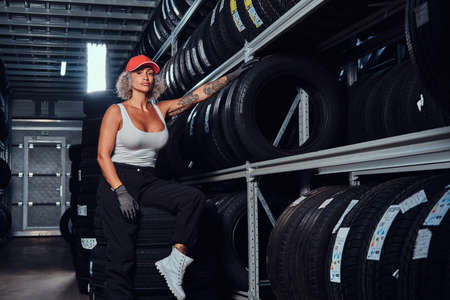 Sexy woman in red cap is chilling at tyre storage while posing for photographer.
