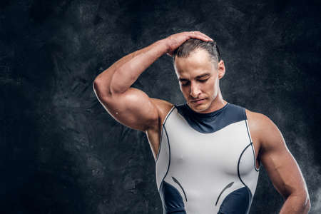 Portrait of muscular handsome man in wetsuit and with cloud of talc around over dark background.