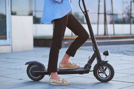 Young woman in stripped blaser is riding her new electrical scooter on the street.