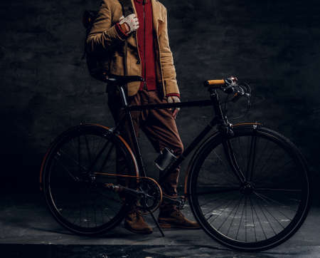 Trendy hipster in jacket is standing at dark photo studio with his retro bike.