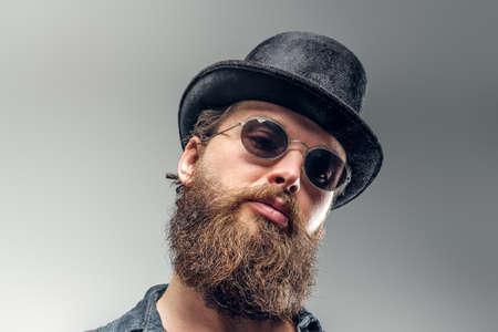 Un homme barbu sérieux en chapeau et lunettes de soleil pose au studio photo. Banque d'images