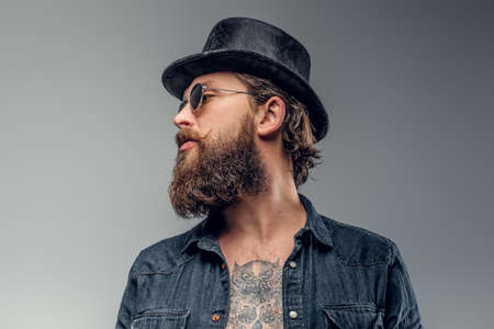 Serious bearded man in hat and sunglasses is posing at photo studio.