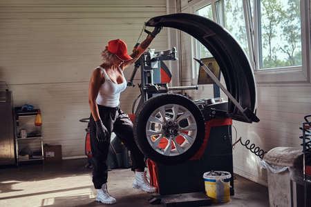 Focused blond woman is doing mans job - she is fixing broken car at workshop. Stockfoto