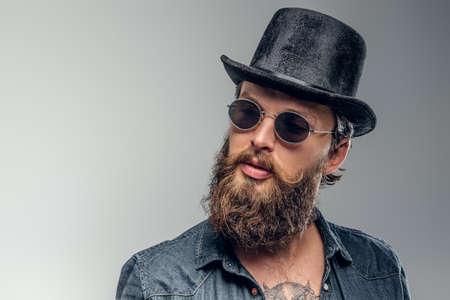 Un homme barbu sérieux en chapeau et lunettes de soleil pose au studio photo.
