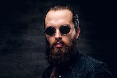 Portrait of brutal bearded man in sunglasses at dark photo studio.