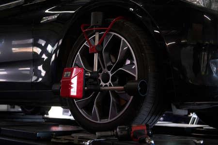 Nahaufnahme-Fotoshooting von Prozess- oder Reifenauswuchten bei dunklem Autoservice. Standard-Bild