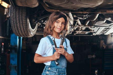 Feliz niña sonriente está de pie debajo del coche en el taller de automóviles con una llave en las manos.