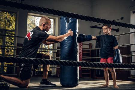 Dark photo shoot of kids training with big punching bag at boxing studio. 스톡 콘텐츠