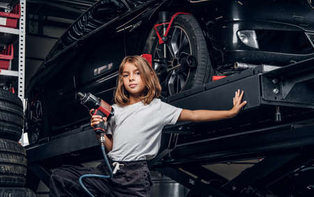 Little cute child is posing for photographer handing pneumatic drill at cars workshop.