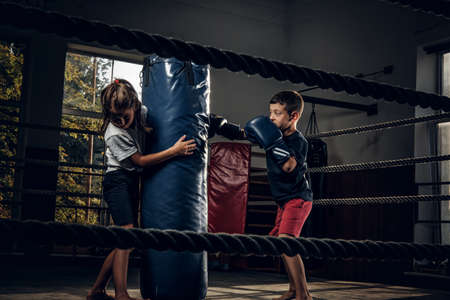 Dark photo shoot of kids training with big punching bag at boxing studio. Stockfoto
