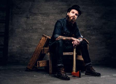 Ernster bärtiger Mann mit Hut sitzt mit Axt in den Händen.