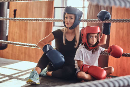 Young cute girl in helmet and her beautiful female boxing trainer are posing for photographer on the ring.