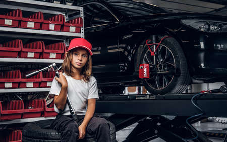 Shelf with tools, shiny car and little girl in hat with big wrench in hands.