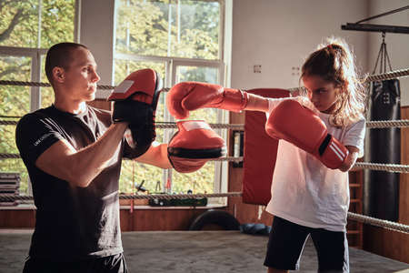 Young boxer trainer is training new girl boxer for special competitions. Banco de Imagens
