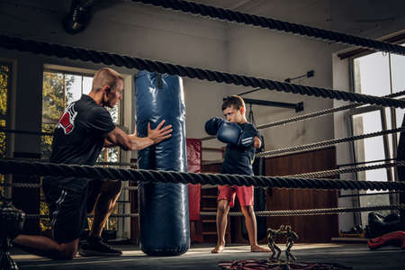 Little child have a serious boxing training with trainer and punching bag.