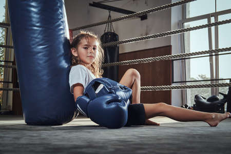 Little tired girl with blue helmet is resting on the ring next to punching bag.