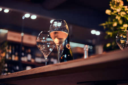 Wine glasses on the bar table, one glass is empty, but the second one is filled with white wine. Banque d'images
