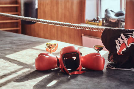 There are prizes on sunny boxing ring - cups and tshirt, and also equipment like red gloves and helmet. Foto de archivo - 131286018
