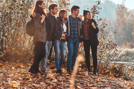 Few friends are enjoying sunny autumn weather while hiking in the forest.
