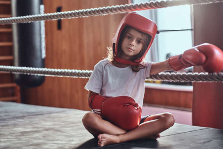Sportive young girl is sitting on sunny ring wearing her eguipment - helmet and boxing gloves. Stockfoto