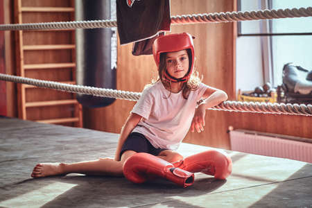 Beautiful kid girl is sitting on boxing ring wearing boxer uniform - gloves and helmet.