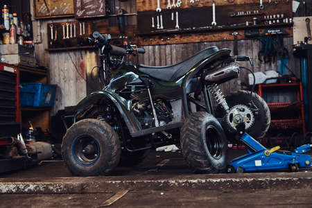 ATV with broken wheel at auto service workshop is waiting to be fixed.