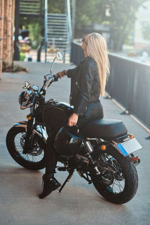 Portrait of beautiful woman in sunglasses and leather clothing on the motorbike. Фото со стока
