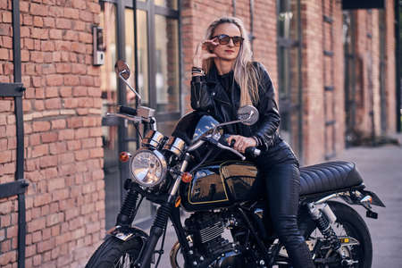 Stylish mature female is posing on photographer on her new shiny retro bike. Фото со стока