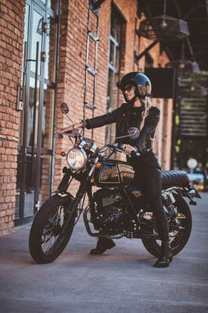 There are sexy mature woman in sunglasses and black protective helmet on the her motorbike.
