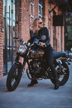 There are sexy mature woman in sunglasses and black leather clothing on the bike.