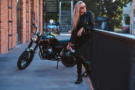 Sexy blond woman is posing for photographer while standing next to her bike. Фото со стока
