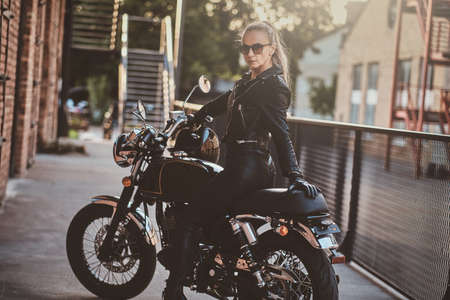Stylish female biker is sitting at her black bike while posing for a photoshoot on the street.