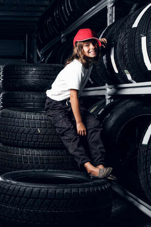 Happy smiling girl in cap is sitting on tyres at dark tyres warehouse.